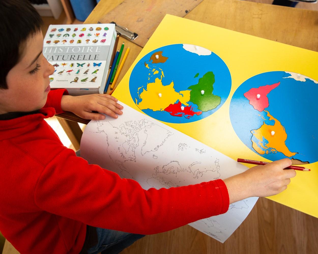 Enfant travaillant à l'aide d'une mappemonde