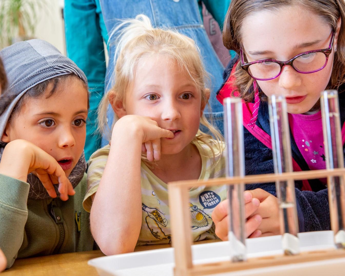 3 enfants observant avec attention des tubes à essai