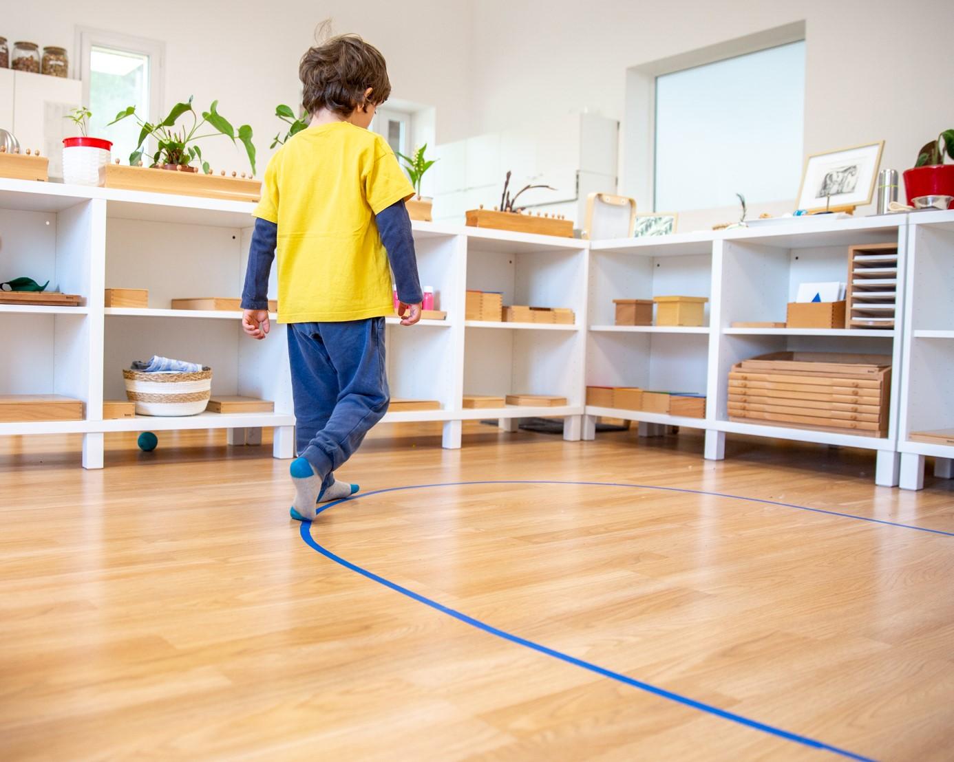 Enfant qui marche sur une ligne bleue tracée au sol