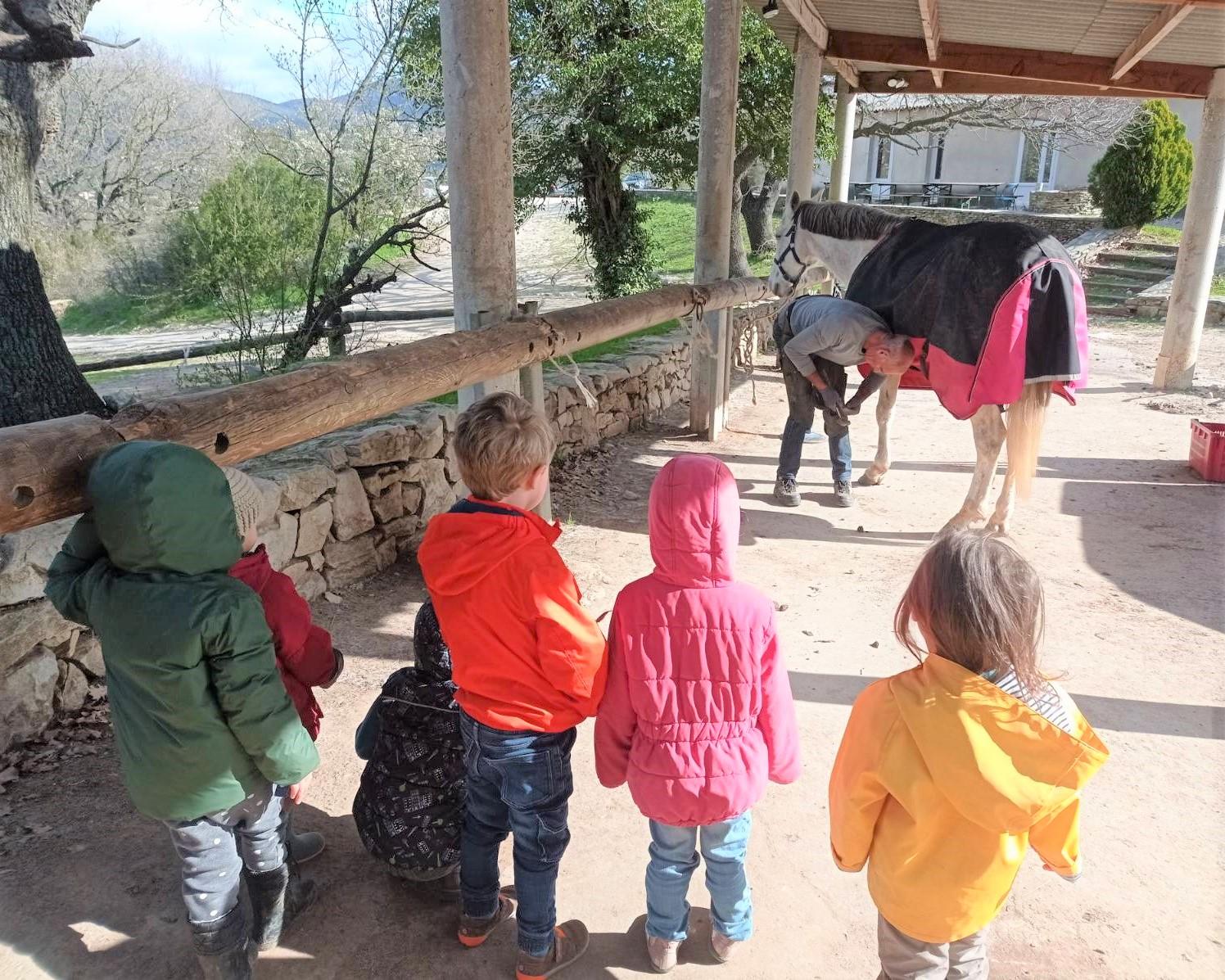 Maréchal ferrant en action devant les enfants